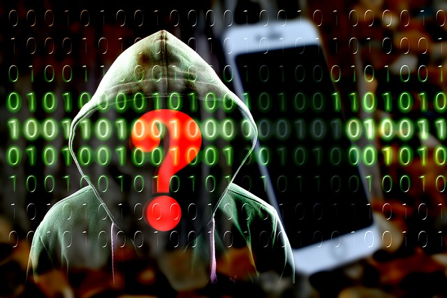 Image of hooded person masked behind binary code with red question mark obscuring his/her face, they are standing next to a smart phone.